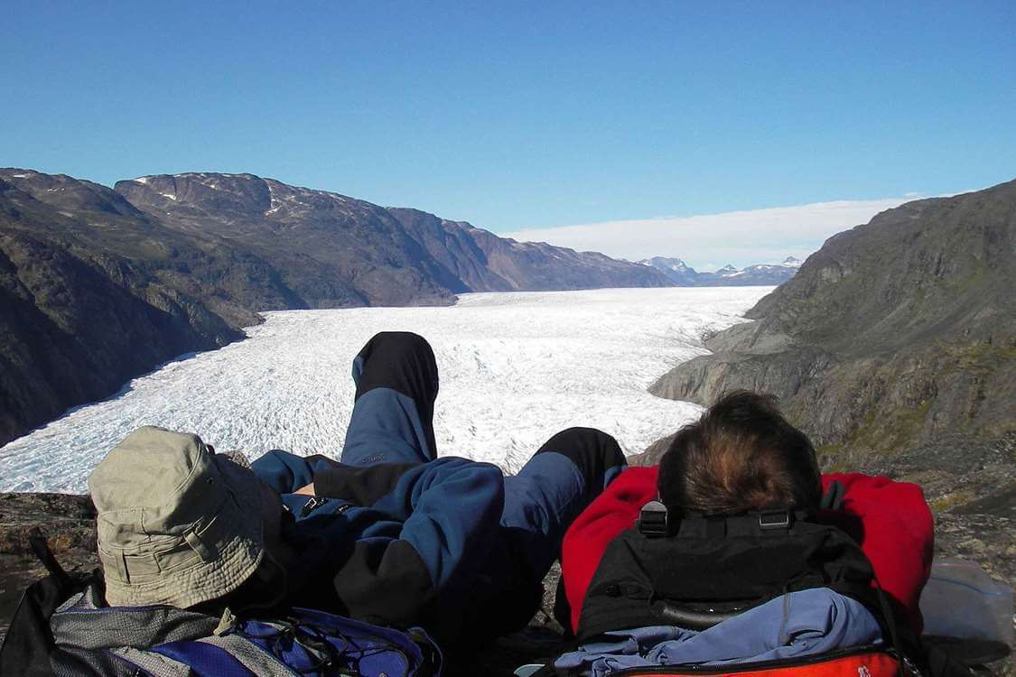 Two hikers looking over a fjord in South Greenland. Photo by Tasermiut South Greenland Expeditions, Visit Greenland