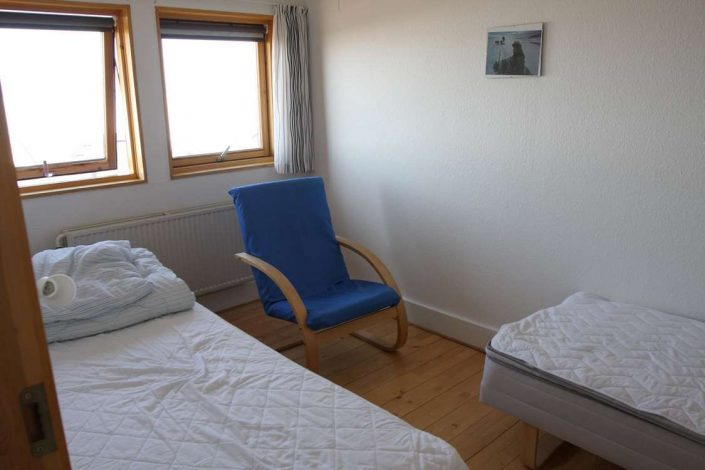Comfortable bedroom with two single beds and an armchair. Photo by Iherit Accommodation, Visit Greenland