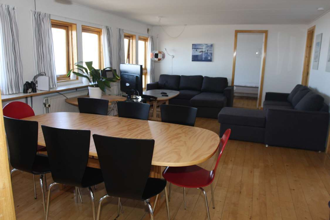 Bright living area with dining area and couches. Photo by Iherit Accommodation, Visit Greenland