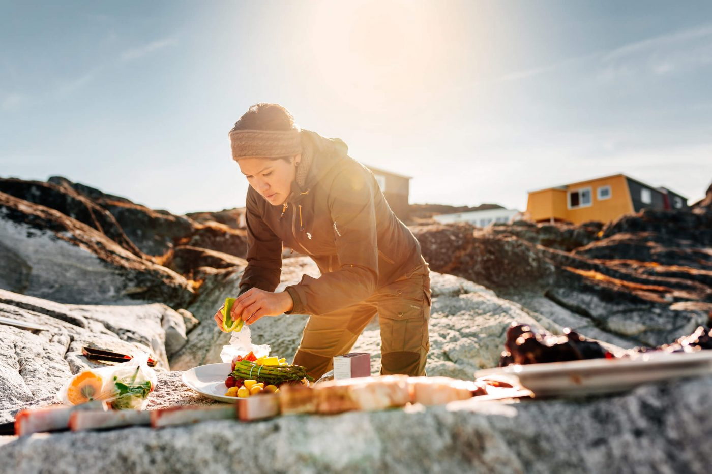 Woman preparing Greenlandic specialties on the rocks on the beach by Inuk Hostels in Nuuk in Greenland. By Rebecca Gustafsson