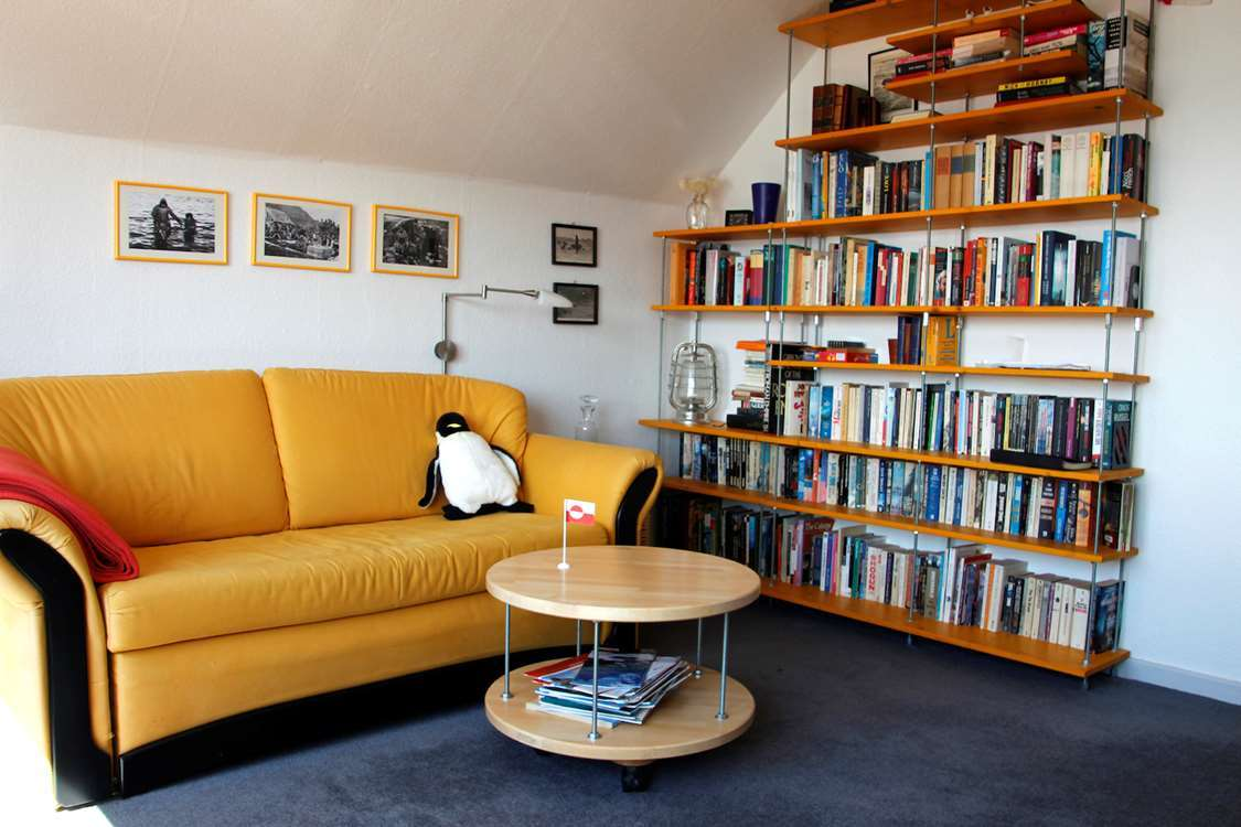 Inside view of Isikkivik house with a small Greenlandic flag on coffee table. Photo by Isikkivik
