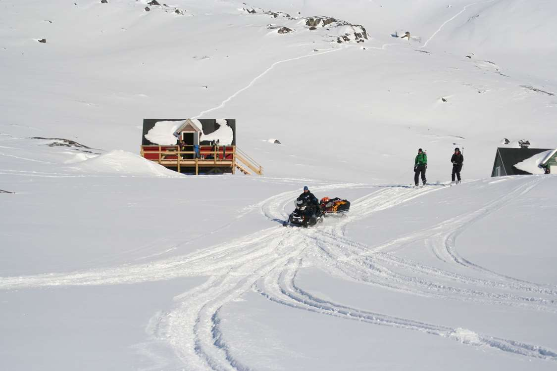 Snowmobile dragging skiers across the snow. Photo by Kangerluarsunnguaq Ski Center