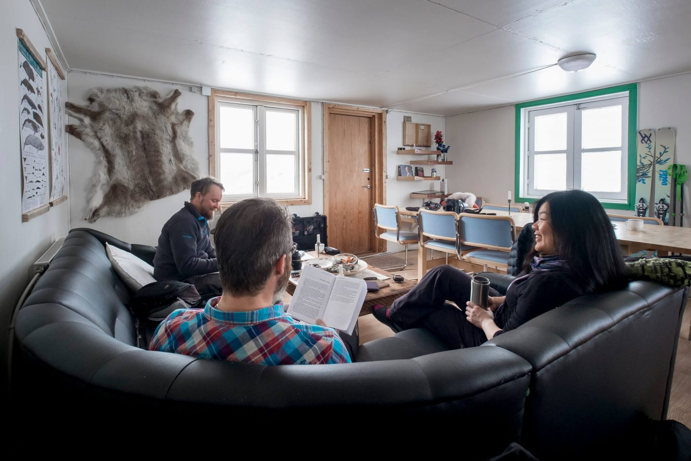 Guests relaxing in couch in lounge and dining area at Kulusuk Hostel in East Greenland. Photo by Icelandic Mountain Guides