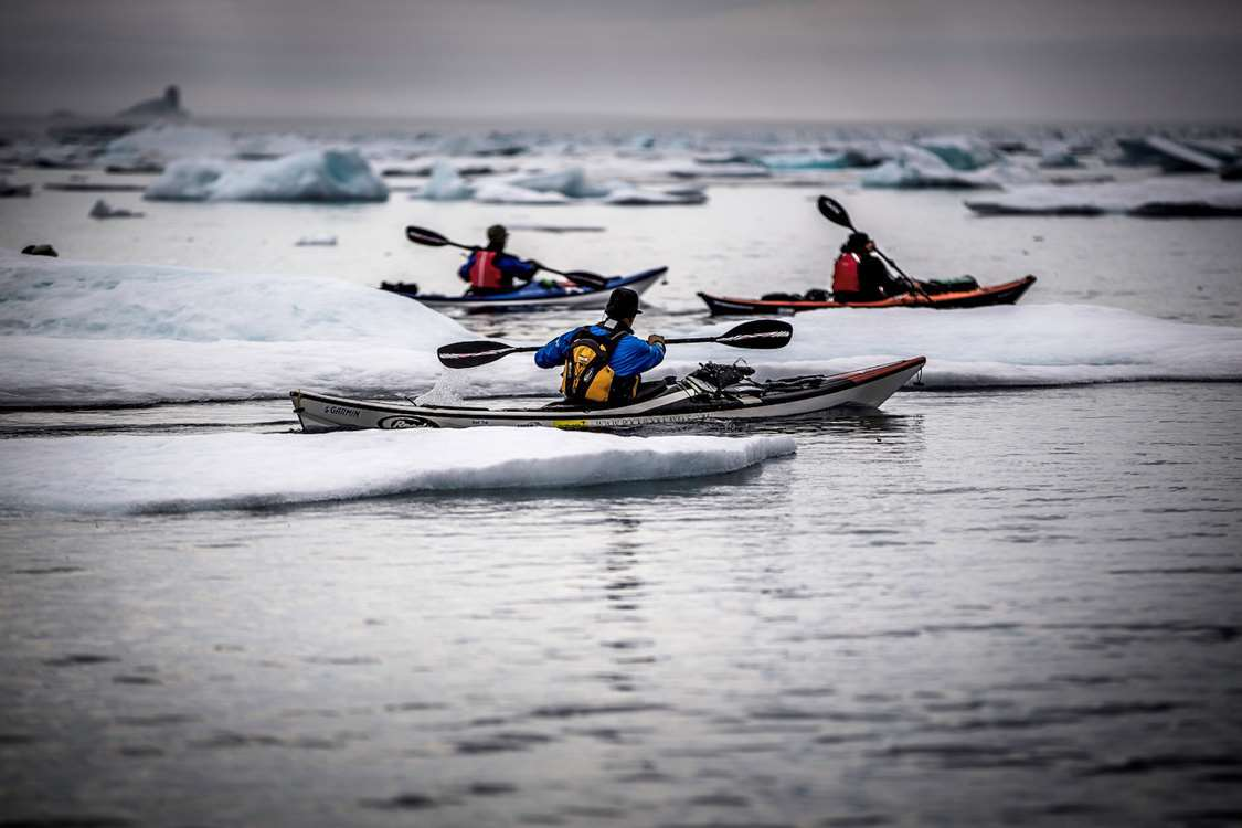 Kayakers among ice floes near Tasiilaq in East Greenland. Photo by Mads Pihl - Visit Greenland