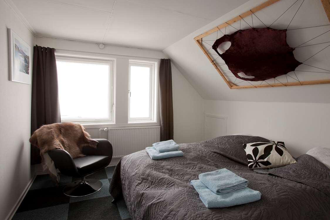 Double bedroom with sealskin hanging on the wall at Hotel Nordlys in Ilulissat. Photo by North Greenland Adventure