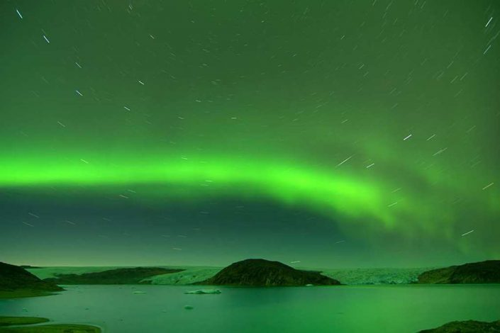 Long exposure photograph of the stars and northern lights above South Greenland. Visit Greenland