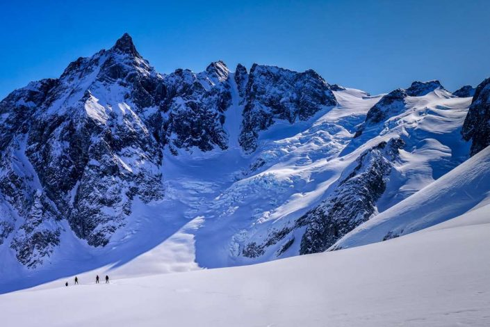 Hikers in front of mountain in snow-covered East Greenland. Photo by Pirhuk - Greenland Expedition Specialists