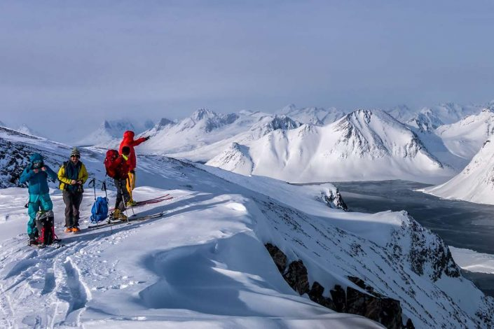 Skiers looking at mountain in horizon in East Greenland. Photo by Pirhuk - Greenland Expedition Specialists