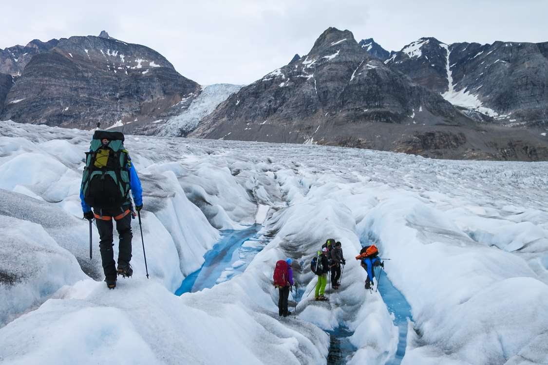 Hikers hiking on glacier in East Greenland. Photo by Pirhuk - Greenland Expedition Specialists