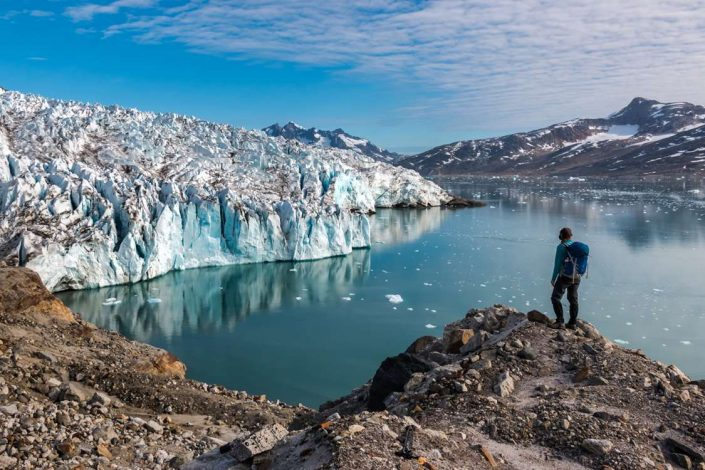 Hiker looking at Knud Rasmussen glacier in East Greenland. Photo by Pirhuk - Greenland Expedition Specialists