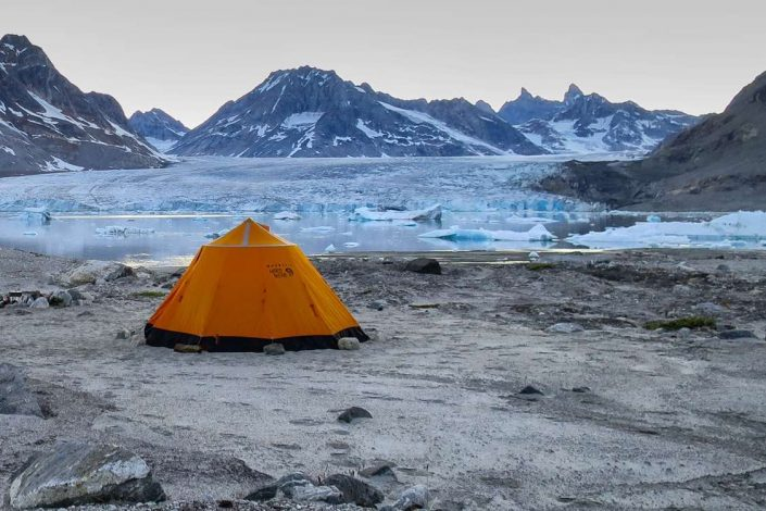 Orange tent camping by Knud Rasmussen glacier in East Greenland. Photo by Pirhuk - Greenland Expedition Specialists
