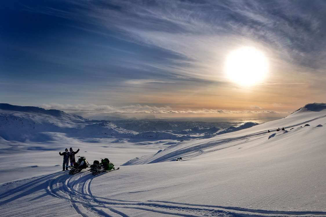 Two snowmobilers in the backcountry near Sisimiut in Greenland. Photo by Mads Pihl, Visit Greenland