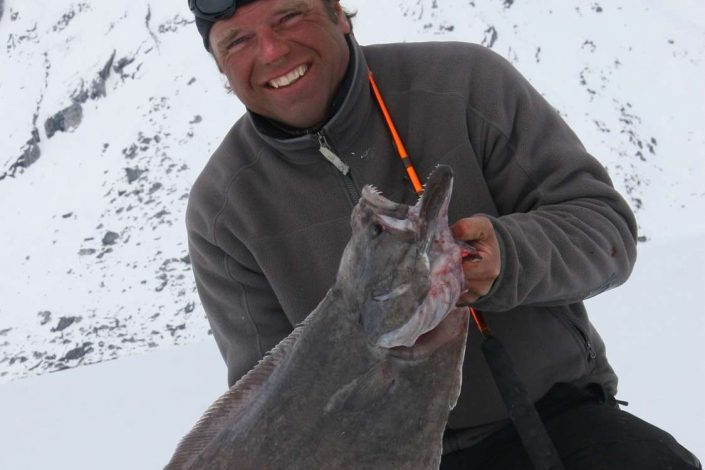 Lars proudly presenting his catch from a fishing trip. Photo by Arctic Dream, Visit Greenland