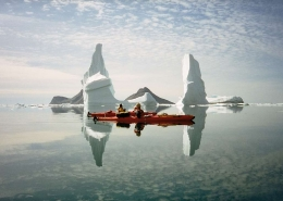 Two people kayaking next to large icebergs in crystal clear water. Photo by Arctic Dream