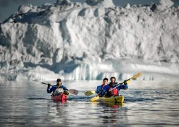 Two kayaks paddling near an iceberg in the Disko Bay in Greenland. By Mads Pihl