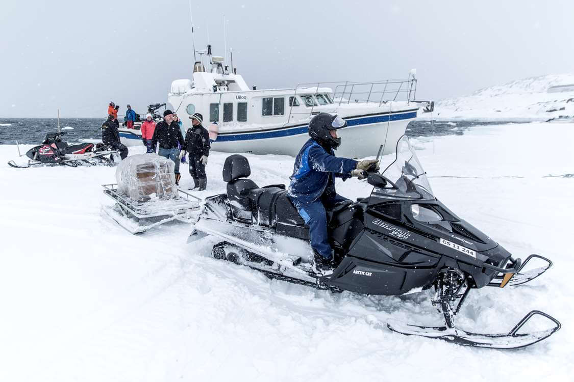 Person on a snow mobile in East Greenland in winter. Visit Greenland