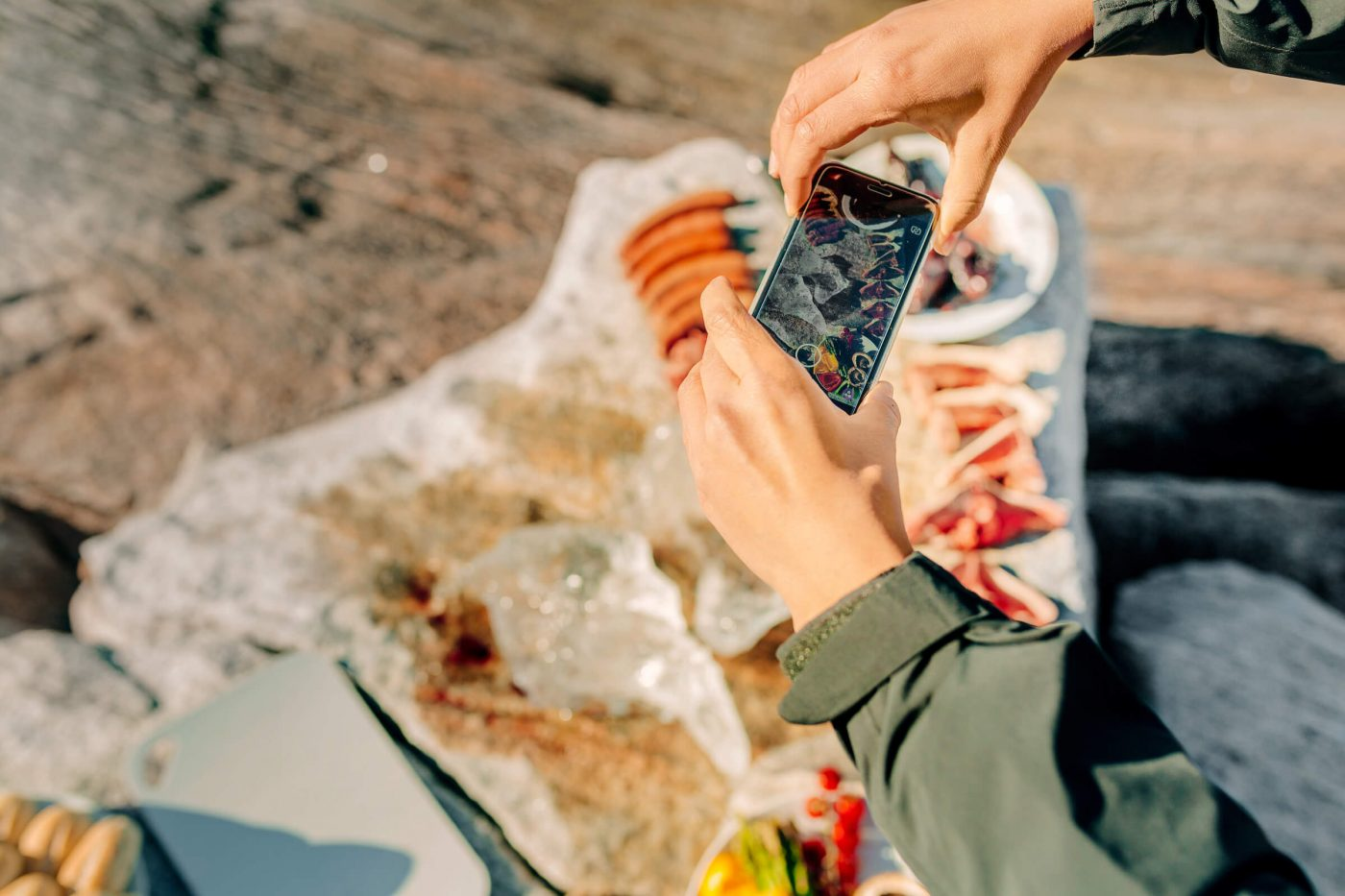 Woman taking a picture of greenlandic food on the rocks in Nuuk in Greenland, by Mads Pihl